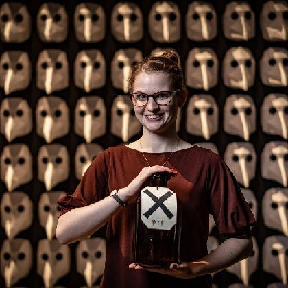 Museumspädagogin steht lächelnd vor der Pestmaskenwand und hält eine Apothekerflasche in den Händen