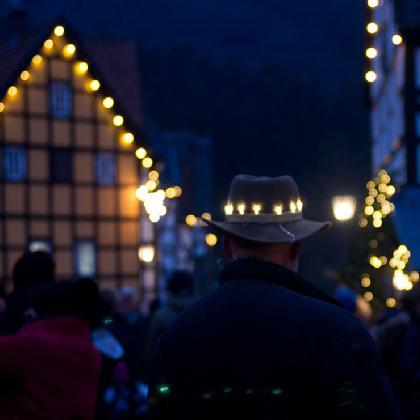Ein Mann mit beleuchtetem Hut vor einem Fachwerkhaus