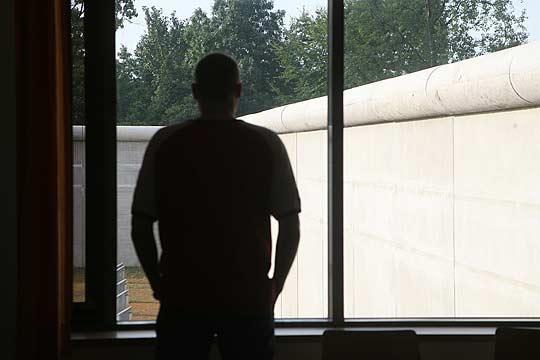 Foto: Mann schaut durchs Fenster auf Mauer