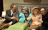 Theaterszene: Ältere Herrschaften sitzen auf einem Bett