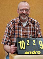 Ein Mann zeigt lachend den Spielstand auf der Punktetafel