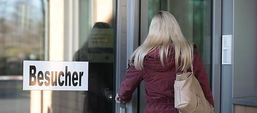 Eine Frau steht vor einer Glastür mit der Aufschrift