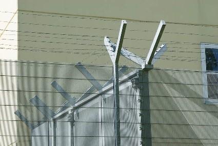 auf dem Bild ist der obere Teil eines Sicherheitszaunes mit Stacheldraht zu sehen