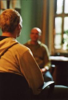 Auf dem Bild ist ein Einzelgespräch zwischen einem Therapeuten und einem Patienten zu sehen.