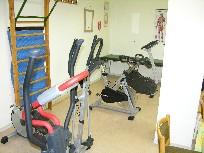 Auf dem Bild ist das Inneren eines Therapieraumes mit einigen Gerätschaften zu sehen. Auf einem der Geräte sitzt eine Physiotherapeutin.