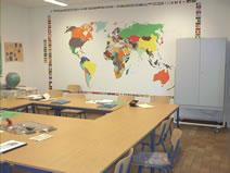 Auf dem Bild ist ein weiteres Schulzimmer zu sehen. An der Wand hängt eine große Weltkarte.