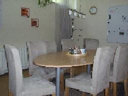 Auf dem Bild ist der Tisch zu sehen, an dem eine Helferkonferenz in der Nachsorgeambulanz stattfindet. Der Tisch ist in einem hellen Holzton, während die Stühle einen hellgrau bis weißen Überwurf haben.