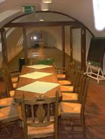 Auf dem Bild sieht man im Hintergrund die Kegelbahn des Sozialzentrums. Im Vordergrund steht ein Tisch mit Stühlen.