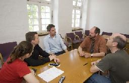 Auf dem Bild sind vier Psychologen und der leitende ärztliche Direktor bei ihrer täglichen Gesprächsrunde zu sehen.