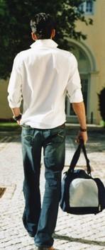 Auf dem Bild ist ein Patient zu sehen, der eine Reisetasche bei sich hat und auf dem Weg in die Klinik ist.