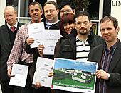 Sieben Personen halten Zertifikate und ein Foto der Forensik