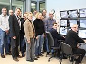 Mehrere Personen vor einer Bildschirmwand