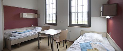 Blick in ein Doppelzimmer mit vergitterten Fenstern