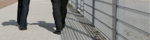 Ausschnitt: zwei Personen laufen an einem Zaun entlang