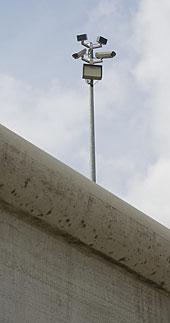 Ein Kameramast hinter einer Betonmauer