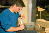 Das Foto zeigt eine Person beim Arbeiten mit Holz.