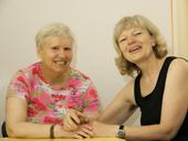 Das Foto zeigt zwei lachende Frauen.