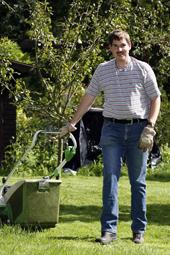 Das Foto zeigt einen Mann beim Rasenmähen.