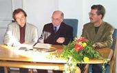 Das Foto zeigt drei Personen in einem persönlichen und fachlichen Austausch.