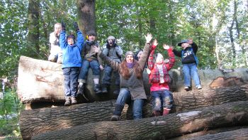 Die Schüler und Schülerinnen der Waldgruppe sind auf umgestürzten Baumstämmen und winken