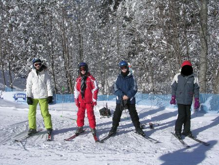 Vier Schüler beim Üben vor der Fahrt auf den Skiern.