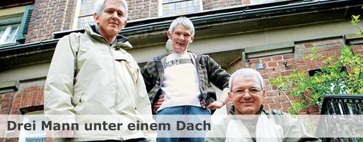 Diese Foto zeigt drei Männer vor einem alten Backsteinhaus.