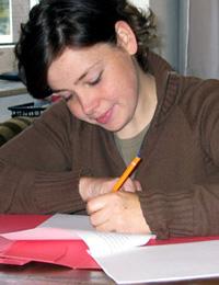 Schülerin am Schreibtisch beim Schreiben ihrer Facharbeit