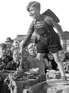 Das rasante Wachstum der Schülerzahlen durch die Aufnahme der Flüchtlinge und Vertriebenen sowie die Zerstörung von Schulen im Bombenkrieg machen vielerorts den Neubau von Schulen nötig. Das Bild zeigt die Grundsteinlegung der Alexanderschule in Raesfeld 1949 (Ausschnitt) / LWL-Medienzentrum für Westfalen