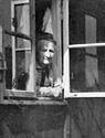 Frau am Fenster einer Nissenhütte im Altenheim des Sozialwerks Stukenbrock / Fotoarchiv: Gerd Plückelmann, Witten